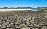 Cracked, dry and exposed lake bottom  in foreground of bed of Lower Klamath Lake, California with small patch of remaining water in background against backdrop of blue sky and distant barren hills.