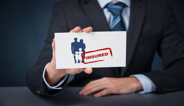 Insured family concept. Insurance agent with family silhouette on card and printed stamp insured.