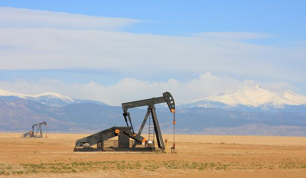 A Pump jack pumping oil from an oil well in the plains with snow capped mountains in the background.