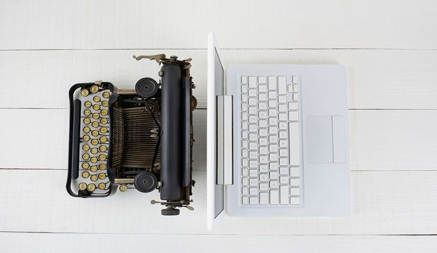 Overhead shot of and old fashioned typewriter back-to-back with a modern laptop computer on w white wood desk.