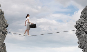 Young confident businesswoman walking on rope above gap