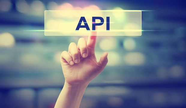 API concept with hand pressing a button on blurred abstract background