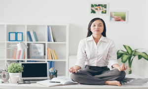 Female office worker meditating on her work place