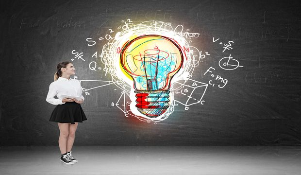 Woman standing near blackboard with giant colorful light bulb sketch pictured on it with formulas surrounding it. Concept of the next big thing