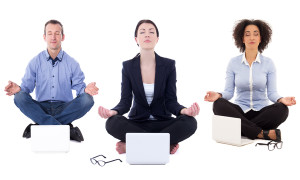 young business people sitting in yoga pose with laptops isolated on white background