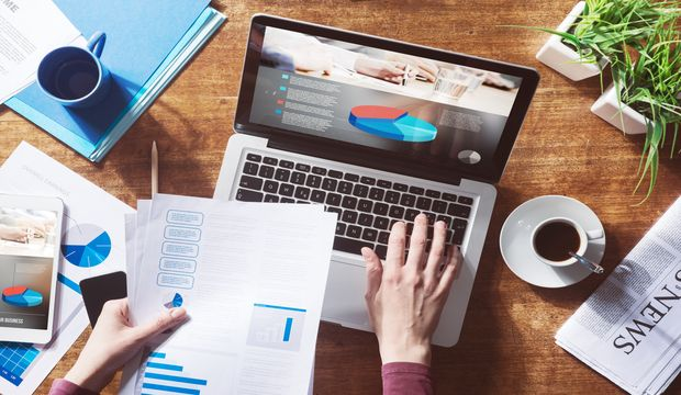 Financial report with pie chart and data on a laptop with business woman's hands at work