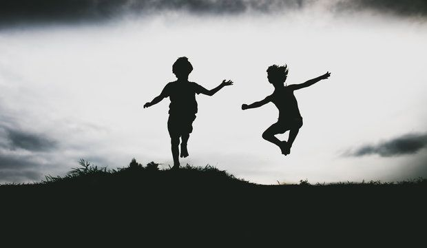 Silhouettes of kids jumping from a sand cliff at the beach. Active healthy kids enjoying their time at the beach. Fraternal twins playing together. Friends having fun during summer vacation. Nice day at the lake.