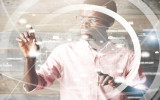 Visual effects. Future technology touch screen interface. High technology concept. Serious African American office worker using futuristic digital device pointing on sensor screen. Selective focus