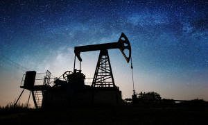 Silhouette of oil pump is pumping crude oil on the oil field in the night under sky with stars and Milky Way. Oil industry equipment