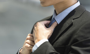 Close up detail of businessman adjusting his tie.