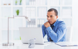 African American businessman sitting in his office and using computer.
